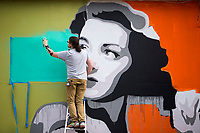 NWA Democrat-Gazette/JASON IVESTER<br /> Steve Adair works Tuesday, March 21, 2017, on his mural, &quot;Uptown Dapper,&quot; on the side of the apartment residents' garage at Uptown Fayetteville. Adair began the mural on Monday and will finish by the end of the week. He also has plans of a second mural at the new development which will feature apartments, restaurants and shops.