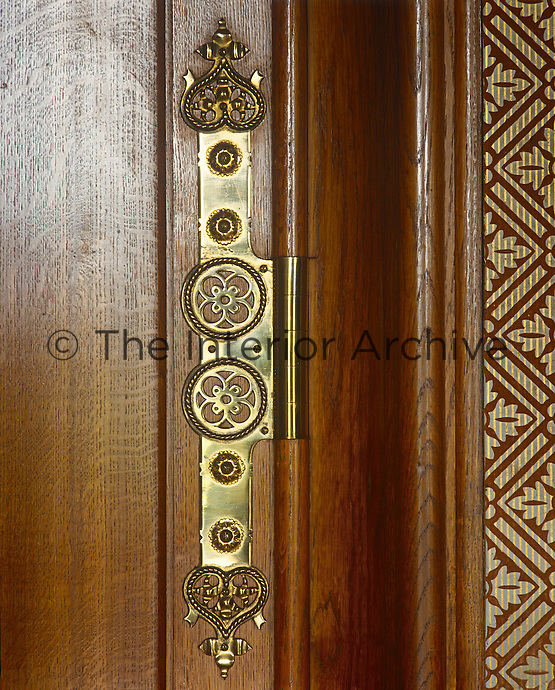 An ornamental brass hinge adorns a wooden door