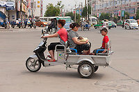 Daytime landscape view of people riding a motorized tricycle on a road in Bozhou in Qiáochéng Qū in Anhui Province.  © LAN