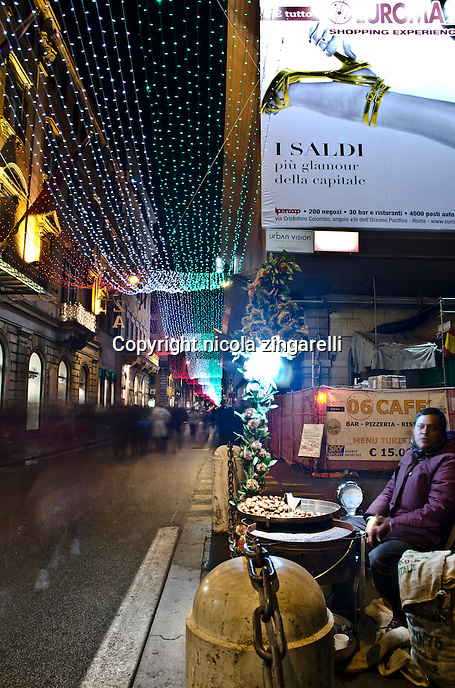 A man, probably from Pakistan or India is selling roasted chestnuts in Via del Corso, Rome's biggest shopping street.