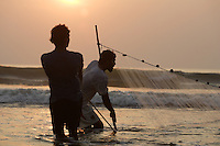 Pair of Beach fishermen pulling one end of Gill net through surf, Goa, Arabian sea, India