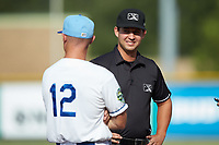 Base umpire Clay Williams chats with Burlington Royals manager Brooks Conrad (12) prior to the game against the Johnson City Cardinals at Burlington Athletic Stadium on July 15, 2018 in Burlington, North Carolina. The Cardinals defeated the Royals 7-6.  (Brian Westerholt/Four Seam Images)