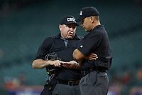 Home plate umpire Wes Hamilton (left) confers with third base umpire Michael Banks during the NCAA baseball game between the Missouri Tigers and the Texas Longhorns in game eight of the 2020 Shriners Hospitals for Children College Classic at Minute Maid Park on March 1, 2020 in Houston, Texas. The Tigers defeated the Longhorns 9-8. (Brian Westerholt/Four Seam Images)