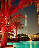 UNITED ARAB EMIRATES, Dubai, Shangri-La Hotel, illuminated swimming pool with trees at night on the rooftop of the Shangri-La Hotel with the Burj Khalifa building in the background