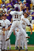 LSU Tigers third baseman Tyler Hanover #11 jumps to high five teammate Kurt McCune #39 before the continuation of their suspended NCAA Super Regional baseball game against Stony Brook on June 9, 2012 at Alex Box Stadium in Baton Rouge, Louisiana. LSU defeated Stony Brook 5-4 in 12 innings. (Andrew Woolley/Four Seam Images)