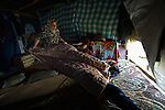 Fadia, who escaped fighting in Aleppo, Syria, picks up blankets in the morning in her family's shelter in the Aamer al Sanad refugee settlement in Kab Elias, a town in Lebanon's Bekaa Valley which has filled with Syrian refugees. Two of her ten children were killed in Syria's civil war. <br /> <br /> Lebanon hosts some 1.5 million refugees from Syria, yet allows no large camps to be established. So refugees have moved into poor neighborhoods or established small informal settlements, such as Aamer al Sanad, in border areas. International Orthodox Christian Charities, a member of the ACT Alliance, provides support for refugees in Kab Elias, including a community clinic.