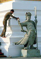 A worker cleaning at the Grand Palace in Bangkok, Thailand. In front an impressive statue stands guard.
