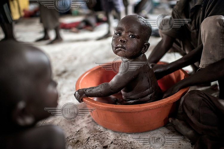 A refugee baby gets a bath in a basin at the Imvepi reception centre in northern ganda.