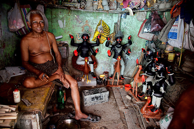 Sculptor Satish Das sits in his workshop in Kumortuli. This is a traditional potters' quarter in northern Kolkata, the capital of the east Indian state of West Bengal. This fascinating district is named for the kumars (sculptors) who create puja effigies of the Hindu gods that will eventually be ritually immersed in the holy Hooghly river. .Straw frames are created, clay is added over it and then fashioned and painted when dry. .After immersion many of the effigies are recovered by the workshops to be re-invigorated for a second use..This Kolkata neighbourhood, not only supplies clay idols of Hindu gods and goddesses to various pujas in Kolkata and its neighbourhoods, but a number of idols are exported overseas..Kumortuli images are generally ordered well in advance and there a few for off-the-shelf sale. Nowadays, Kumortuli's clientele has extended to America, Europe and Africa, among the Indian communities living there. .In 2006, Kumortuli supplied 12,300 clay deities of goddess Durga. This potter's town supplies images to about 90 countries worldwide with new nations joining the list every year. Many East European countries, where religious ceremonies were previously banned, have started buying images from Kumortuli. .Additionally, hundreds of agents in Kolkata service NRIs seeking idols from Kumortuli..In Kolkata, the icon-artisans mostly dwell in poor living conditions however by virtue of their artistic productions these potters have moved from obscurity to prominence. Sculptor Satish Das sits in his workshop in Kumortuli. This is a traditional potters' quarter in northern Kolkata, the capital of the east Indian state of West Bengal. This fascinating district is named for the kumars (sculptors) who create puja effigies of the Hindu gods that will eventually be ritually immersed in the holy Hooghly river. .Straw frames are created, clay is added over it and then fashioned and painted when dry. .After immersion many of the effigies are recovered by the workshops