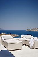 Crea wicker sun loungers on a terrace at the Villa Orpheus located on the Greek island of Mykonos.