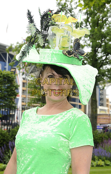 racegoer.The Royal Ascot Ladies Day racing event, Day 3, Ascot Racecourse, Ascot, Berkshire, England..June 21st, 2012.half length green dress hat bottle jar butterfly butterflies umbrella .CAP/CAN.©Can Nguyen/Capital Pictures.