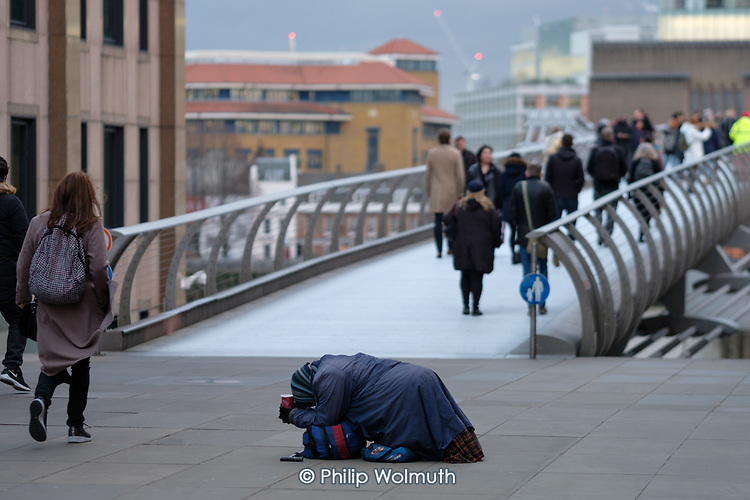 Woman begging at the Thames Millenium Bridge, City of London.