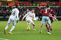 Pictured: Gylfi Sigurdsson of Swansea, team mate Modou Barrow (L) and Aaron Cresswell of West Ham (R) Saturday 10 January 2015<br />