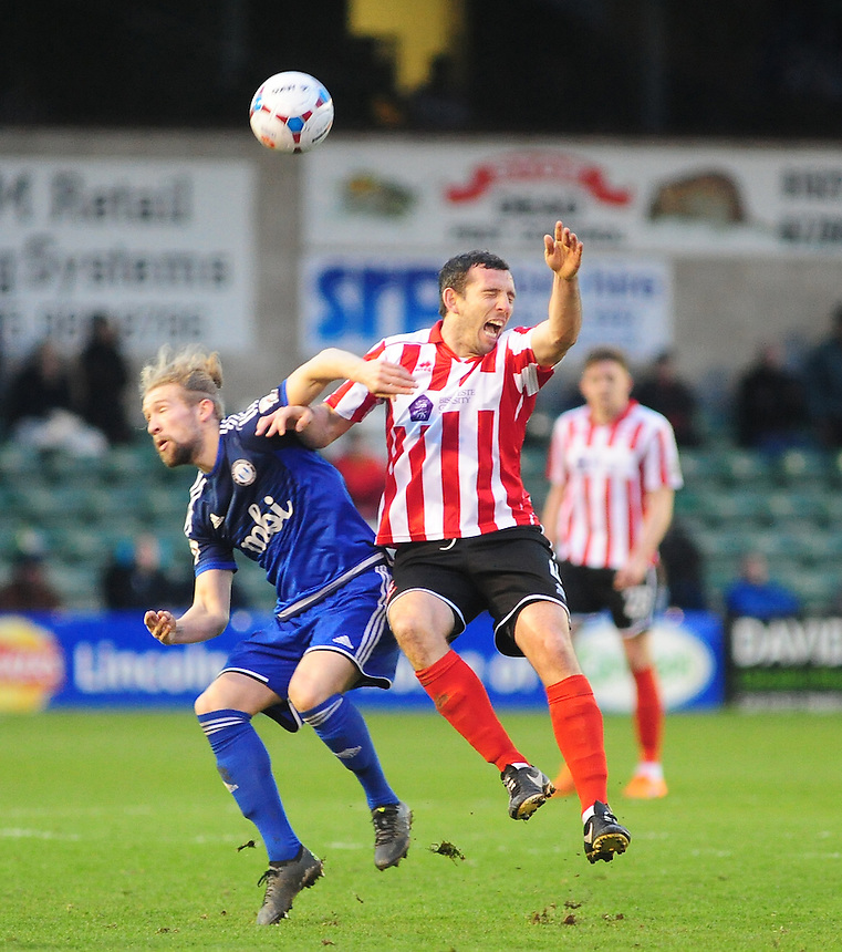 Lincoln City's Craig Stanley is fouled by FC Halifax Town's Kingsley James<br /> <br /> Photographer Andrew Vaughan/CameraSport<br /> <br /> Football - Vanarama National League - Lincoln City v FC Halifax Town - Saturday 26th December 2015 - Sincil Bank - Lincoln<br /> <br /> &copy; CameraSport - 43 Linden Ave. Countesthorpe. Leicester. England. LE8 5PG - Tel: +44 (0) 116 277 4147 - admin@camerasport.com - www.camerasport.com