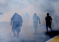 Mar 14, 2014; Gainesville, FL, USA; Crew members for NHRA pro stock driver Chris McGaha covered in smoke during qualifying for the Gatornationals at Gainesville Raceway Mandatory Credit: Mark J. Rebilas-USA TODAY Sports