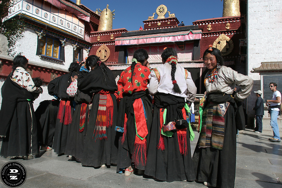 Tibetan nomad women prepare to pray in front of the Jokhang (also known in Tibetan as Tsuglhakhang) at  Barkhor Square in Lhasa, Tibet. The Jokhang is considered the most revered religious structure in Tibet.  Photograph by Douglas ZImmerman