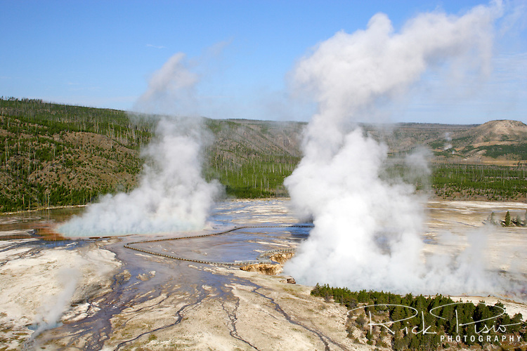 "The Midway Geyser Basin in Yellowstone National Park features the Grand Prismatic Spring and Excelsior Geyser. After a visit in 1899 Rudyard Kipling referred to the Midway Geyser Basin as ""Hell's Half Acre."""