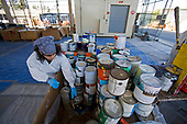 Worker sorts oil based and latex paint cans at S.A.F.E  Collection Center, Sun Valley, Bureau of Sanitation for the City of Los Angeles, California, USA