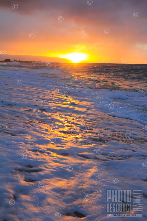 A blazing sunset lights up the sky with seafoam in the foreground at Ke Iki beach, North Shore, O'ahu.
