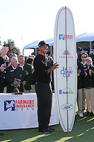 28 JAN 13  Tournament Champion Tiger Woods holds the winners surfboard on18 green at the conclusion of Sunday's Final Round of The Farmers Insurance Open at Torrey Pines Golf Course in La Jolla, California. (photo:  kenneth e.dennis / kendennisphoto.com)