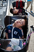 A couple of twins fast asleep in their seats on their mothers bicycle.