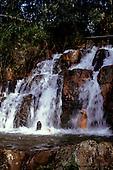 Amazon, Brazil.  A man and a woman enjoying a shower under a waterfall.