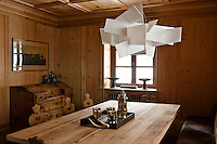 A modern pendant lamp by Foscarini hangs over the table in this otherwise traditional wood panelled dining room
