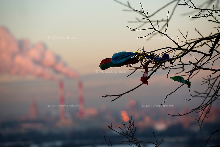 Deflated balloons hang in a tree in front of smokestacks standing above Moscow as viewed from Smotrovaya Ploshadka (Viewing Square) in the Vorobyevy Gory (Sparrow Hills) near Moscow State University in Moscow, Russia.