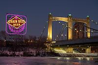 Historic Grain Belt Beer sign and Hennepin Avenue bridge along the Mississippi River in downtown Minneapolis, Minnesota. The sign is lit in Purple and gold to celebrate the Minnesota Vikings playoff run. The sign was refurbished in late 2017.