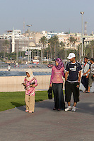 Tripoli, Libya, North Africa - Dress Styles in Contemporary Libya.  Walking in a Public Park near the Green Square, in downtown Tripoli.  Women typically cover their heads with a scarf, but may wear jeans, levis, slacks, or a traditional abaya.  Men wear European or western-style attire.