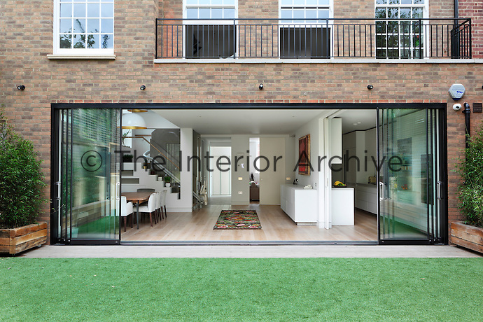 The rear view of a house with a ground floor extension, which provides a terrace on the the flat roof above. The open plan room below has full height sliding glass doors that lead to the garden.