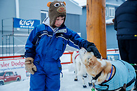 A young race fan pets a Gunna Johnson dog at the finish line in Nome  during the 2017 Iditarod on Friday March 17, 2017.<br /> <br /> Photo by Jeff Schultz/SchultzPhoto.com  (C) 2017  ALL RIGHTS RESERVED