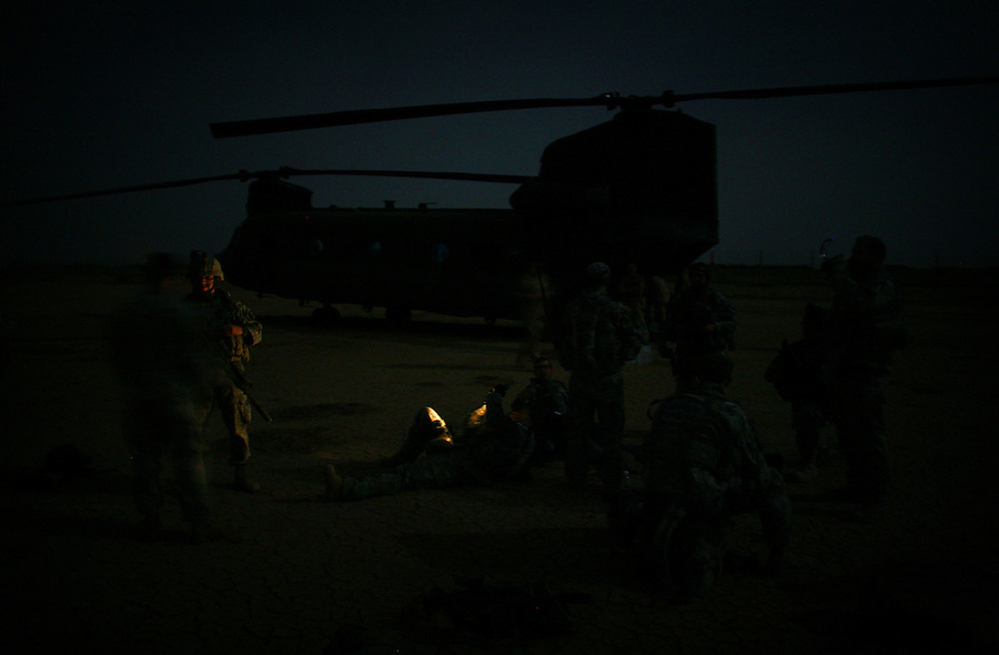 A CH-47 Chinook helicopter waiting in the background, soldiers from 1-12 Cavalry 3HBCT 1st Cavalry Division relax and chat before the start of an air assault mission looking for insurgent prison and training facilities in the countryside near the Diyala provincial capital, Baqubah, on Monday May 28, 2007.