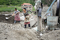 Locals in Heishui town working on a small construction site near to the Heishui River. Construction projects in this area have contributed to a changing landscape on the Tibetan Plateau.  South-east Tibetan Plateau, in Sichuan Province, western China.