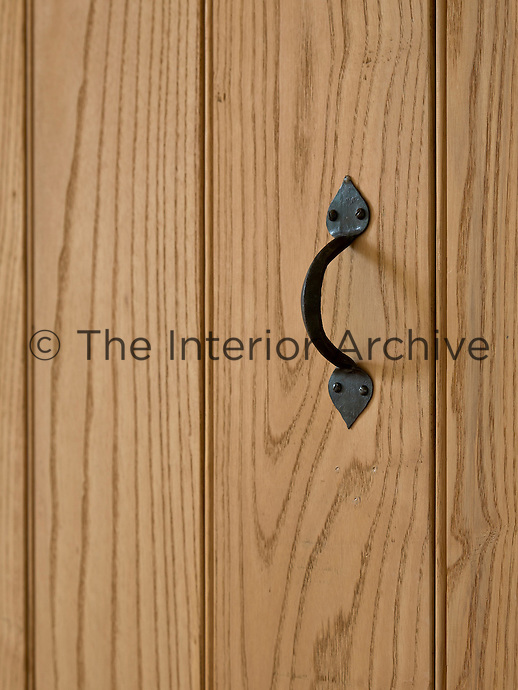 A pine tongue-and-groove door has a traditional black wrought-iron handle