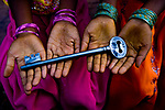 A large iron iron key held across two pairs of children's hands to show scale and colours. Photograph © Santosh Verma