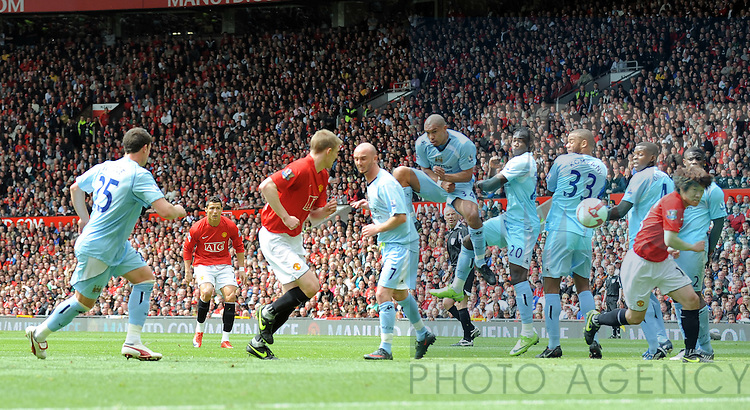 Cristiano Ronaldo of Manchester United scores the first goal from a free kick through the Manchester City wall