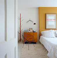 A George Nelson bedside cabinet and a Bertoia wire chair are teamed with a bespoke bed designed by James Biber
