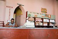 Shopkeeper in his grocery store doing accounting, Trinidad, Sancti Spiritus, Cuba.