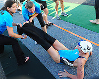 Volunteers help Kathleen Mcinnis out of her wetsuit during Ironman 2010 on Sunday, 9/12/10, in Madison, Wisconsin