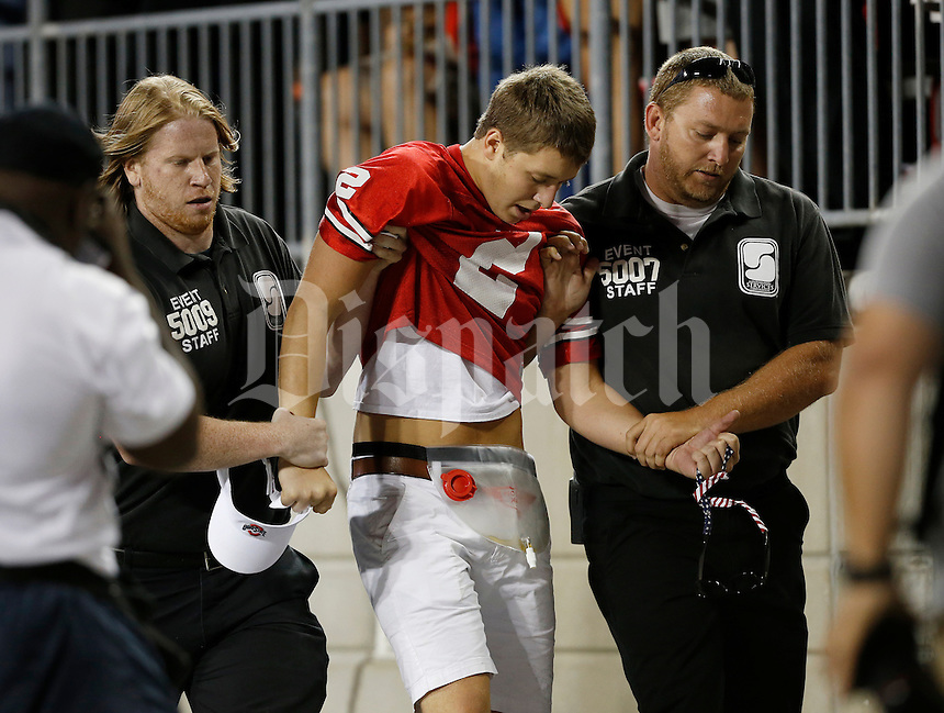 Security guards escort a fan who ran onto the field out of the stadium during the second quarter of the NCAA football game against the Cincinnati Bearcats at Ohio Stadium in Columbus on Sept. 27, 2014. (Adam Cairns / The Columbus Dispatch)