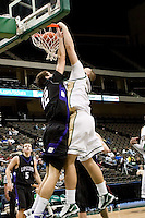 January 14, 2010:    Jacksonville center Szymon Lukasiak (30) dunks over Lipscomb center Milos Kleut (32) during Atlantic Sun conference game action between the Jacksonville Dolphins and the Lipscomb Bisons at Veterans Memorial Arena in Jacksonville, Florida.  Jacksonville defeated Lipscomb 79-73.