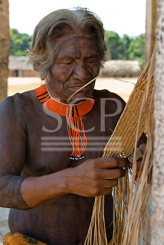 Pará State, Brazil. Aldeia Kikretum. Old man making woven buriti strap.