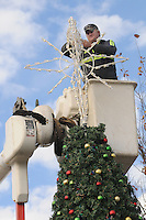 NWA Democrat-Gazette/FLIP PUTTHOFF<br /> PEAK OF THE TREE<br /> Grant Walker works Tuesday Nov. 24, 2015 at the top of the downtown Rogers Christmas tree that city street department employees put up at First and Elm streets. Lights on the tree will be turned on Dec. 4 during the Rogers Christmas parade, said Frankie Guyll, street department superintendent.