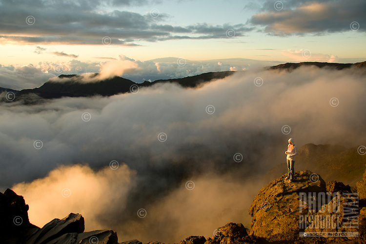 A young woman watches the sun rise from the crater's edge at Kalahaku Overlook in Haleakala National Park, Maui, with the summits of the Big Island's Mauna Kea and Mauna Loa in the distance.