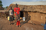 A family poses in front of their shelter in the Doro Refugee Camp in Maban County, South Sudan. Doro is one of four camps in Maban that together shelter more than 130,000 refugees from the Blue Nile region of Sudan. Jesuit Refugee Service provides educational and psycho-social services to both refugees and the host community. <br /> <br /> Misean Cara supports the work of JRS in the Maban camps.