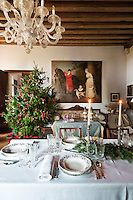 A large murano glass chandelier hangs over the table laid for Christmas dinner in the drawing room