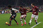 Juan Cuadrado of Juventus with Hakan Calhanoglu and Diego Laxalt of AC Milan for company during the Coppa Italia match at Giuseppe Meazza, Milan. Picture date: 13th February 2020. Picture credit should read: Jonathan Moscrop/Sportimage