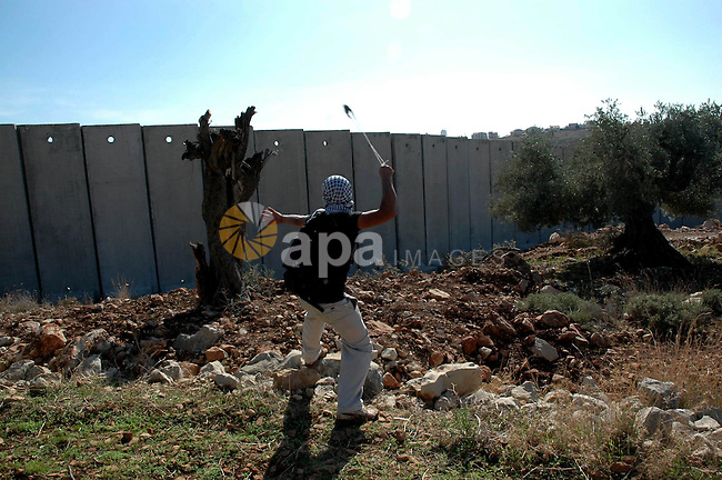 Palestinian uses a sling to hurl stones at Israeli forces during a demonstration against Israel's separation barrier in the West Bank village Nillin near Ramallah on Nov 20, 2009. Photo by Nedal Shtieh