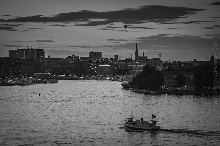Sommarskymning med färja på Stockholms ström i svartvitt..